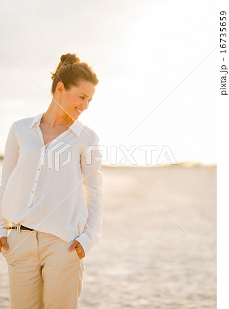 Portrait of happy young woman on beach at the evening looking on
