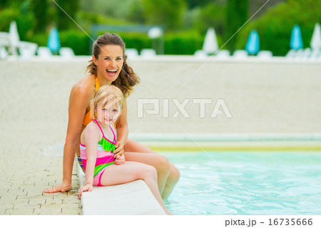 Portrait of happy mother and baby girl near swimming pool