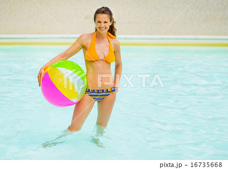 Portrait of young woman with ball standing in swimming pool
