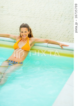 Portrait of happy young woman relaxing in swimming pool