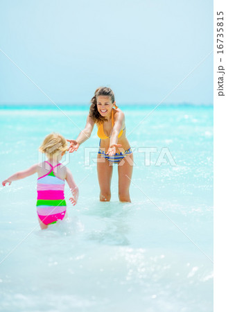 Mother and baby girl playing in sea