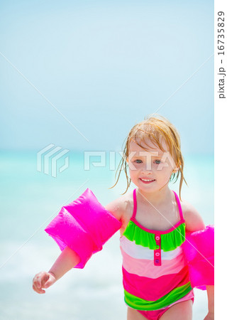 Baby girl in inflatable armband walking at seaside