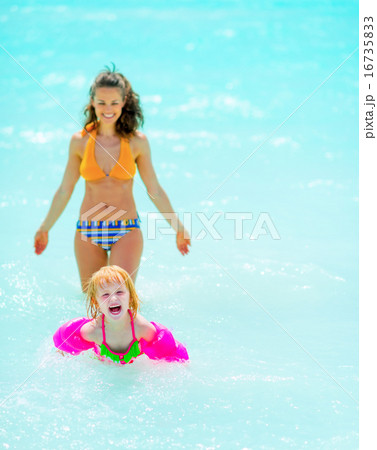 Happy mother and baby girl playing in sea