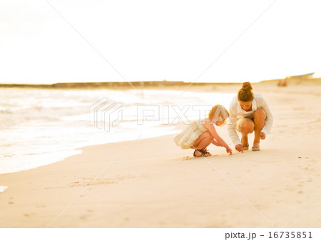 Mother and baby girl drawing on sand on beach at the evening