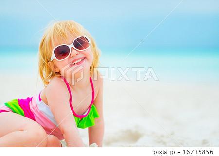 Portrait of happy baby girl in sunglasses on beach