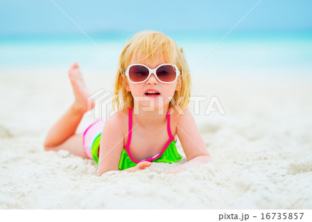 Portrait of baby girl in sunglasses laying on beach