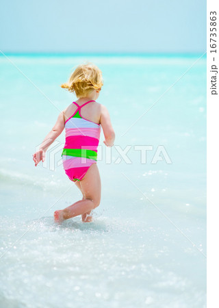 Baby girl playing on sea shore. rear view