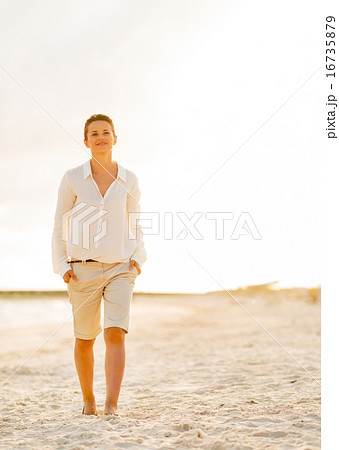 Portrait of happy young woman walking on beach at the evening