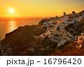 サントリーニ島イアの町並みとエーゲ海に沈む夕日 16796420