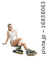 Pretty happy girl with rollerskates sitting on floor against white background 16838063