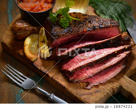 Steak with herbs and beer on a wooden background 16874221