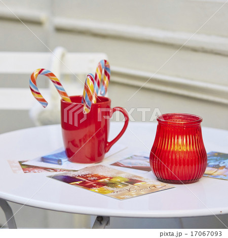 Candle, mug with candy canes and postcardsの写真素材 [17067093] - PIXTA