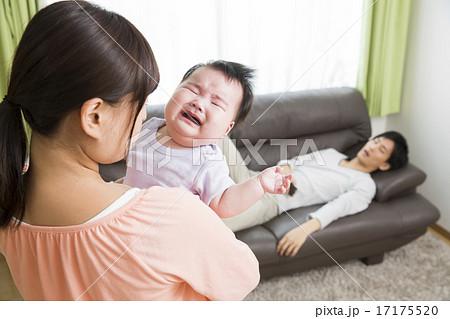 育児イメージ 泣く赤ちゃんをあやすお母さんとソファでスマホをいじる ...