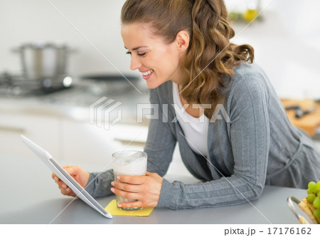 Happy young woman with smoothie using tablet pc in kitchen