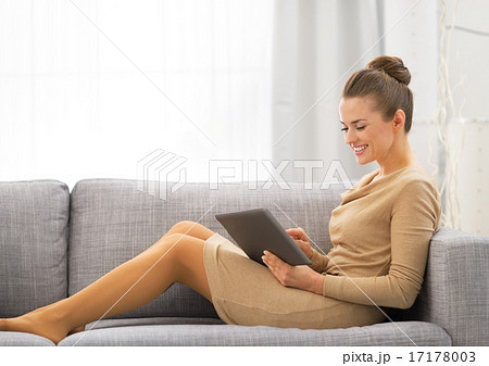 Young woman sitting on sofa and using tablet pc
