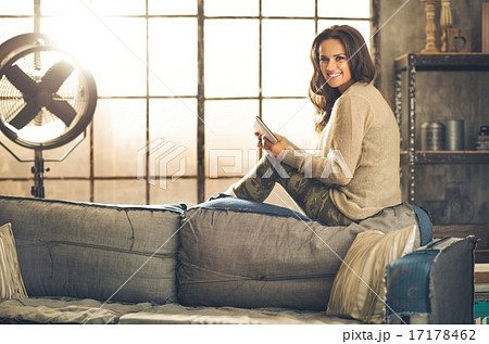 Smiling woman relaxing on sofa back holding a tablet PC in loft