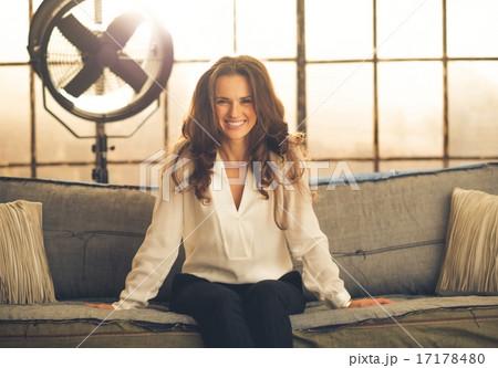 Smiling, elegant woman leaning forward sitting on sofa in loft