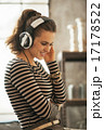 Portrait of happy young woman listening music in headphones in l 17178522