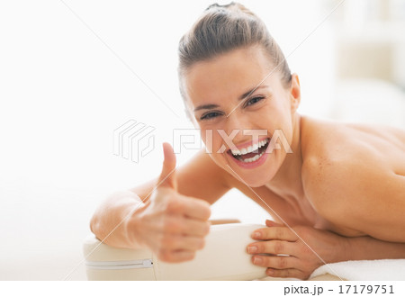 Smiling young woman laying on massage table and showing thumbs u