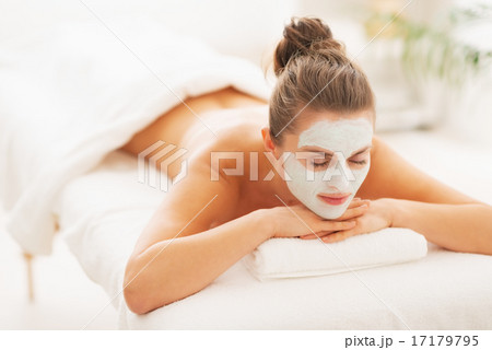 Relaxed young woman with revitalising mask on face laying on mas