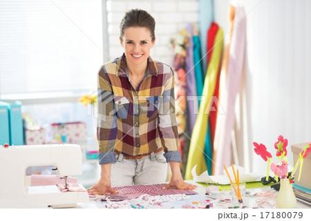 Portrait of happy seamstress in studio