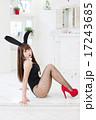 白い部屋を背景にしてカメラ目線で横向きに両膝を立てて座っているバニーガール姿の若い女性 17243685
