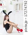 白い部屋を背景にしてカメラ目線で横向きに両膝を抱えて体育座りをしているバニーガール姿の若い女性 17274792