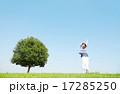 一本木のある原っぱに立つ女性 背伸び 17285250