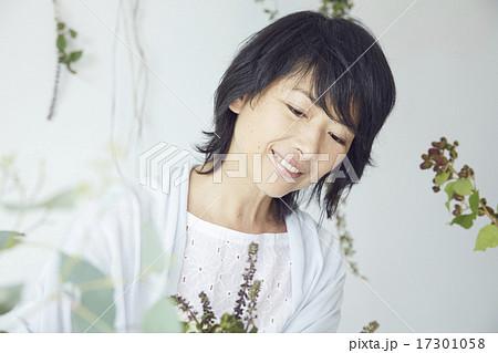 フラワーアレンジメントを楽しむ女性 17301058