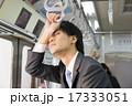 電車内で立ったまま寝るビジネスマン 17333051