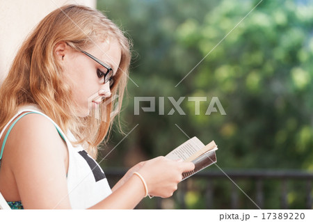 Blond teenage girl on the balcony with book 17389220 for The balcony book
