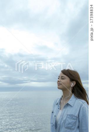 海岸で音楽を聴く笑顔の女性 17398834