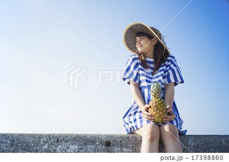 堤防にパイナップルを持って座る女性 17398860