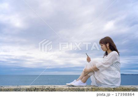 海岸に座って音楽を聴く女性 17398864