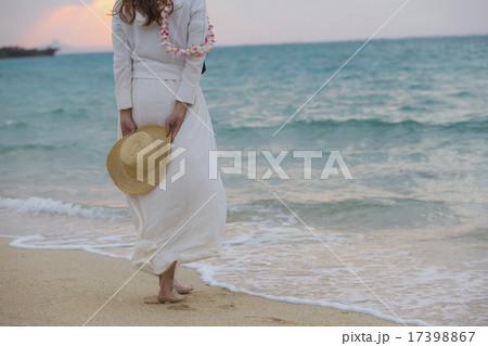 波打ち際で麦わら帽子を持つ女性 17398867