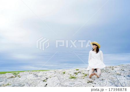 海辺の岩に座る女性 17398878