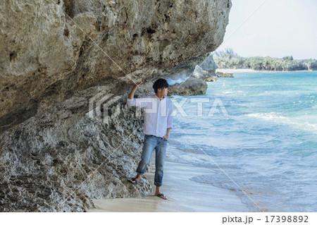 海岸で海を見ている男性 17398892