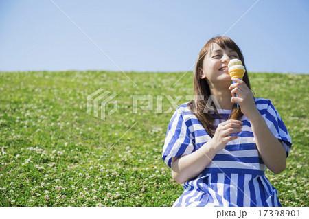 草原に座ってアイスを食べる女性 17398901