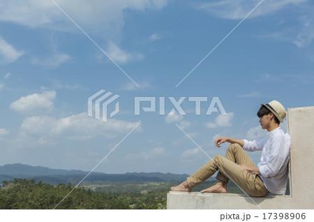 帽子をかぶって座る男性 17398906