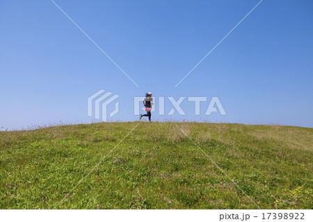 草原をランニングする女性の後姿 17398922