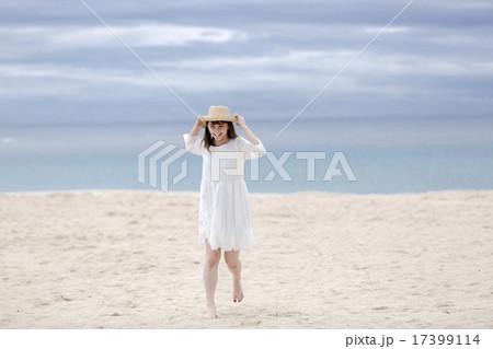 砂浜を歩く笑顔の女性 17399114
