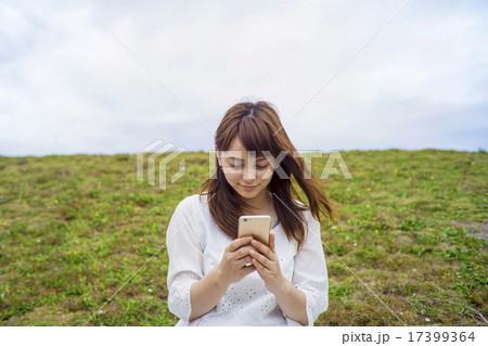 草原に座ってスマートフォンを見る女性 17399364