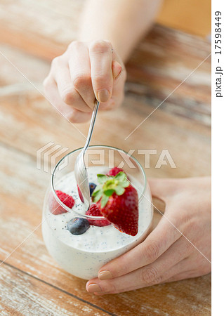 close up of woman hands with yogurt and berries