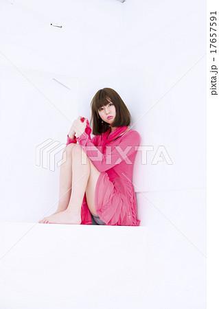 白い背景の段の所で横向きに体育座りをしているカメラ目線の若い女性 17657591