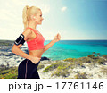 sporty woman running with smartphone and earphones 17761146