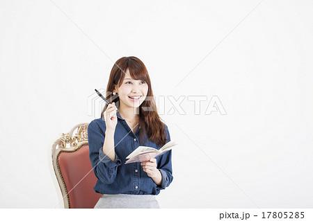 白い背景の前で椅子に座り何か閃いた様子でメモをとっている笑顔の若い女性 17805285