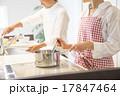 明るいキッチンで料理をする夫婦 17847464