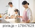明るいキッチンで料理をする家族 17847629