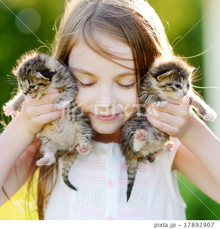 Adorable little girl playing with small kittens