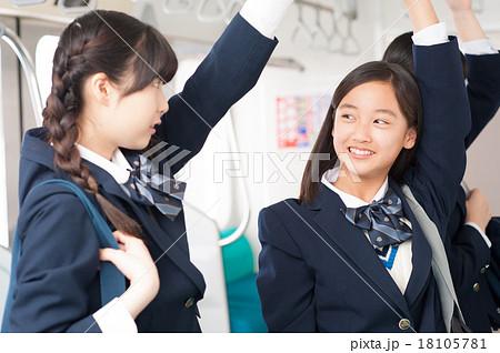 電車の中で会話をする中学生の女の子たち 18105781